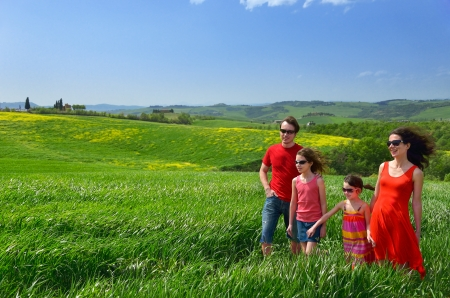 Happy family with children having fun outdoors on green field, spring vacation with kids in Tuscany, Italy