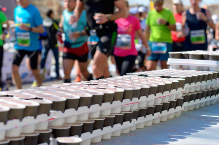 Photo pour Marathon running race runners on road volunteer giving water and isotonic drinks on refreshment point - image libre de droit