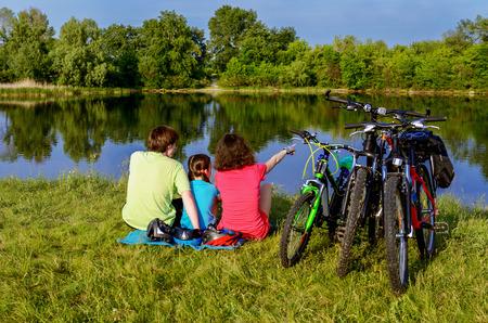 Foto de Family bike ride outdoors, active parents and kid cycling and relaxing near beautiful river - Imagen libre de derechos