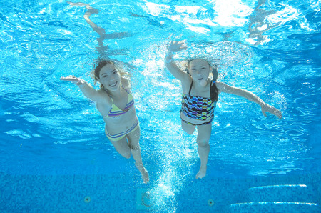 Children swim in pool underwater, happy active girls have fun in water, kids sport on family vacation