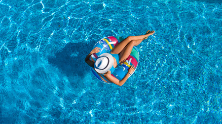 Photo for Aerial top view of beautiful girl in swimming pool from above, relax swim on inflatable ring donut and has fun in water on family vacation - Royalty Free Image