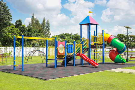 Foto de Colorful playground on yard in the park. - Imagen libre de derechos
