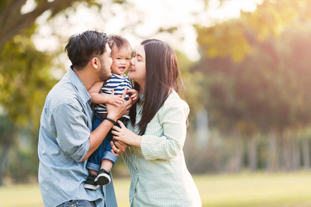 Photo for Happy mother and father kissing his little son in park - Royalty Free Image