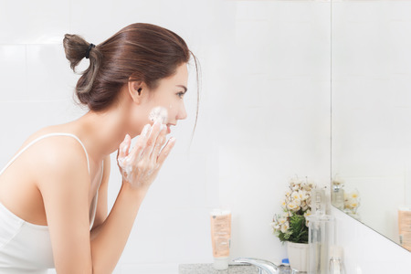 Foto de Woman happy cleanses the skin with foam in bathroom. - Imagen libre de derechos