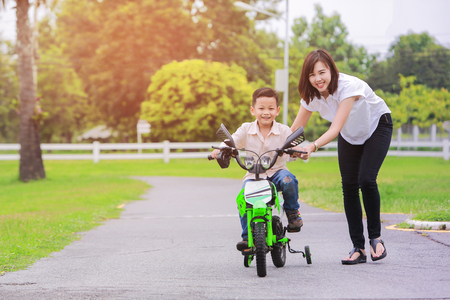 Photo pour Loving mother help her cute son ride a bicycle. - image libre de droit