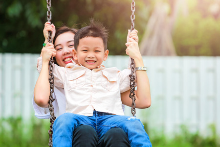 Photo for Happy family having fun on a swing ride at a garden. - Royalty Free Image