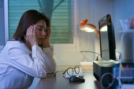 Foto de Young tired business woman headache sitting at computer in workplace. - Imagen libre de derechos