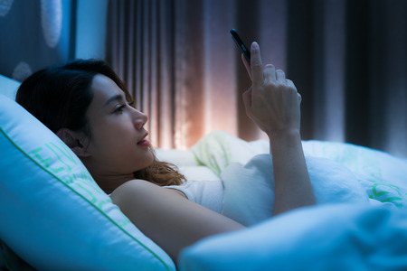 Photo pour Woman on bed late at night texting using mobile phone tired falling sleep. - image libre de droit