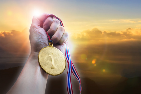 Photo for Businessman hand holding golden coin medal on hill. - Royalty Free Image