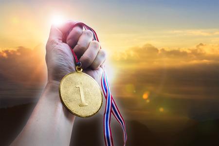 Foto de Businessman hand holding golden coin medal on hill. - Imagen libre de derechos