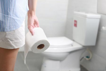 Foto de Woman holds toilet paper roll in front of toilet bowl. - Imagen libre de derechos