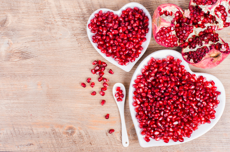 Photo pour Two white heart shaped plates full of fresh ripe juicy pomegranate seeds, little spoon, whole fruit and ripe one on wooden background. - image libre de droit