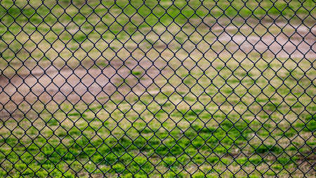 Photo pour Chain link fence in a sports park with grassy field behind it - image libre de droit