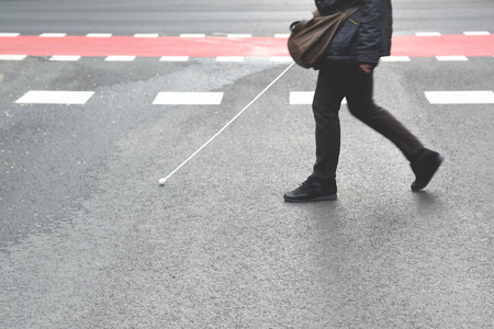 Photo pour Blind person walking with a stick crossing a pedestrian walkway. Empty copy space for Publisher's text. - image libre de droit