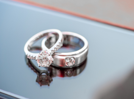 Foto de Two diamond wedding rings reflect on glass - Imagen libre de derechos