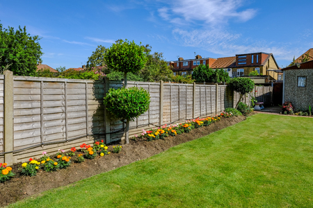 Foto de Backgarden tidy flower bed with fence and  newly mown grass. - Imagen libre de derechos