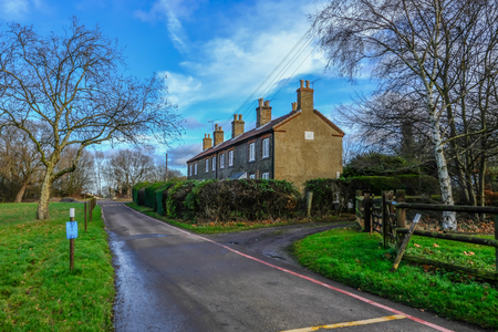 Photo for Hainault Forest, Essex, England, UK  - December 26, 2017: Row of cottages in Epping Forest, used for rangers, taken on a bright blue sky day. - Royalty Free Image