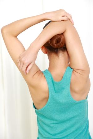 Photo pour young woman doing self shoulder stretch - image libre de droit