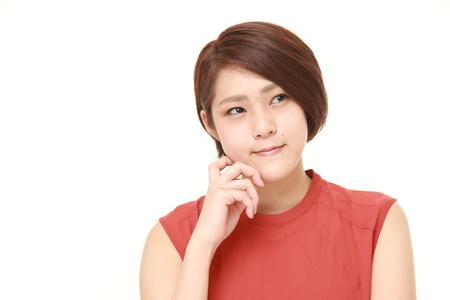 Foto de young Japanese woman thinks about something - Imagen libre de derechos