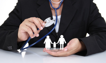 Photo for Businessman holding stethoscope with paper family - Royalty Free Image