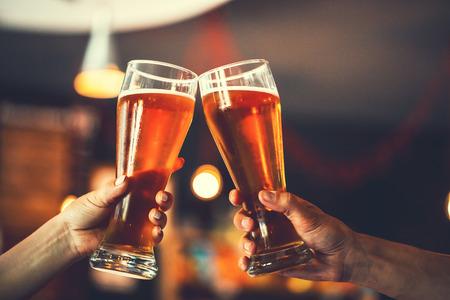 Foto de Two friends toasting with glasses of light beer at the pub. Beautiful background of the Oktoberfest. fine grain. Soft focus. Shallow DOF - Imagen libre de derechos
