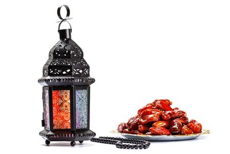 Foto de The Muslim feast of the holy month of Ramadan Kareem. Beautiful background with a shining lantern Fanus and dried dates on white. Free space for your text - Imagen libre de derechos