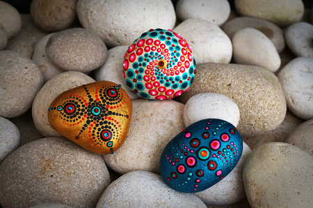 Photo for Beautiful hand painted mandala stones lies on the rocks - Royalty Free Image