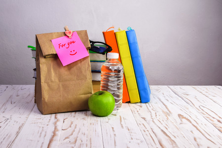 Photo pour paper  lunch bag  with apple,water and books  on desk with  note, - image libre de droit