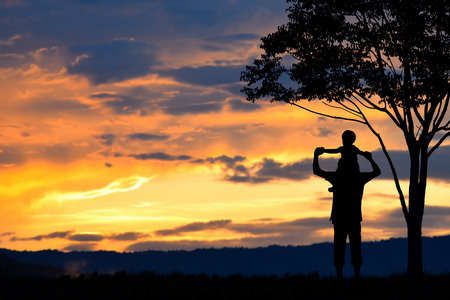 Foto de Father day ,father and son silhouettes play at sunset mountain blurred background - Imagen libre de derechos