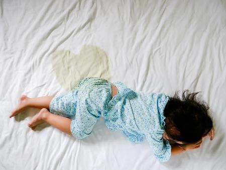 Foto de Child pee on a mattress, Little girl feet and pee in bed sheet, Child development concept , selected focus. - Imagen libre de derechos