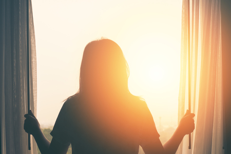 Photo for young woman stand in the bedroom open curtain see sunrise after wake up - Royalty Free Image