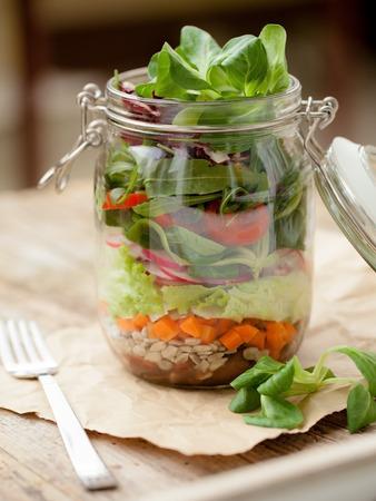 Foto de Lettuce, tomato and other vegetables in glass jar - Imagen libre de derechos