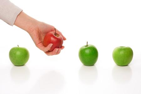 Photo pour Picking different apple among other similar on white - image libre de droit
