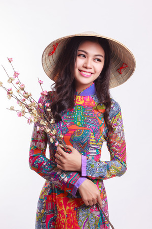 Photo for Beautiful Vietnamese young woman with tradition modern ao dai and palm-leaf conical hat ( non la ) holding cherry blossom at Tet Holiday - Royalty Free Image