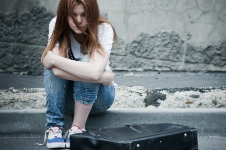 Beautiful young sad girl sitting on asphalt. Photo in cold faded tones