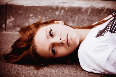 Closeup portrait of a young sad girl lying on asphalt