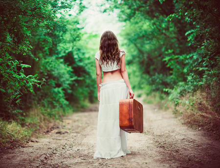 Photo for Young woman with suitcase in hand going away by a rural road - Royalty Free Image