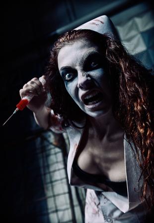 Photo pour Horror shot: the crazy evil nurse (doctor) with syringe in hand. Zombie woman (living dead) - image libre de droit