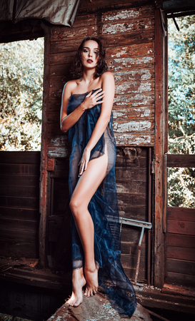 Foto de Sexy beautiful young girl covered in fabric stands in the old train wagon. Full length  - Imagen libre de derechos