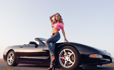 Photo for Sexy alluring young girl dressed in jeans and topic standing at the car (cabriolet). Outdoor portrait on the road at sunset - Royalty Free Image