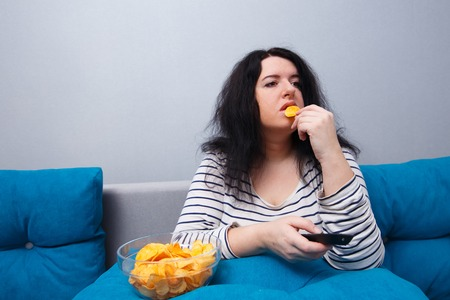 Photo for Fat overweight woman sitting on the sofa, eating chips while wat - Royalty Free Image