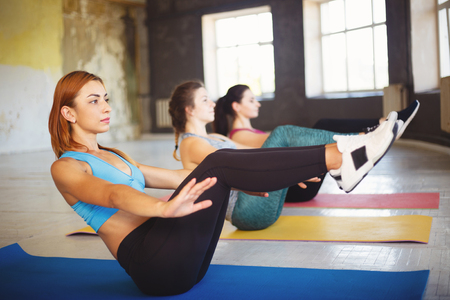 Photo for Sporty women doing abdominal crunches at workout - Royalty Free Image