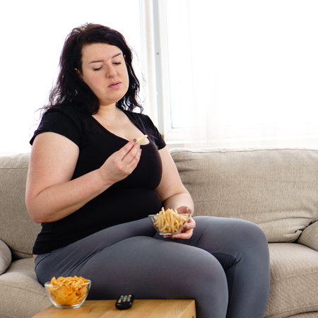 Photo pour Overweight woman with tv remote and junk food - image libre de droit