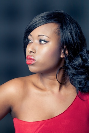Beautiful young black woman wearing a red dress, profile shot, isolated on black