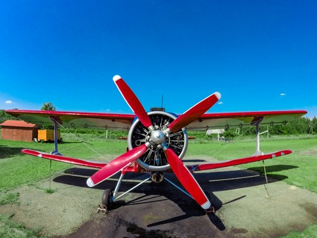 Photo for A small red sports red aircraft on a covered grass field in a sunny clear day. - Royalty Free Image