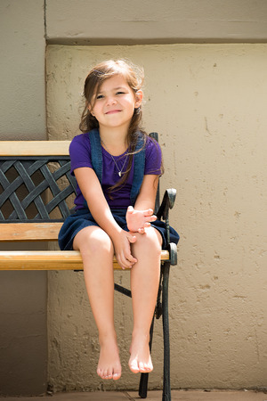 A little girl sits on a bench outside in the back garden of her home.