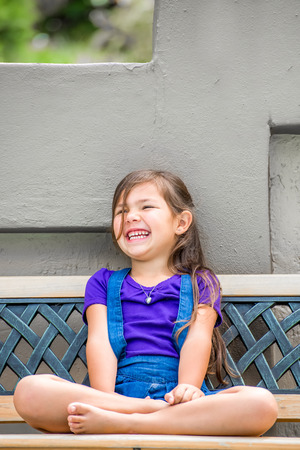 A pretty little girl,with long dark hair, and purple shirt, sits on an outside bench in the garden with her legs folded, while laughing with joy.