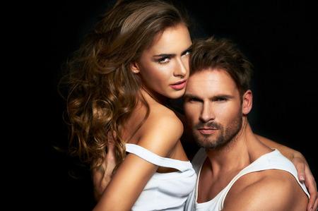 Foto de Beautiful couple in white posing over a black fashion background - Imagen libre de derechos