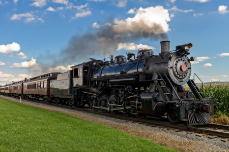historic steam train passes through the fields