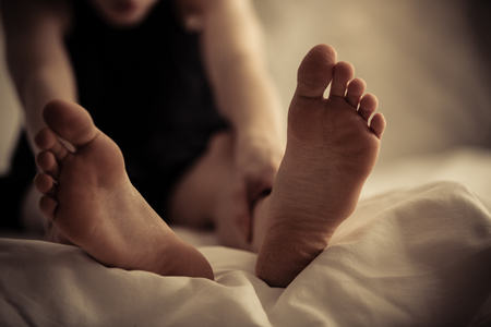Single person sitting up with front selective focus view of feet in foreground on bed sheet